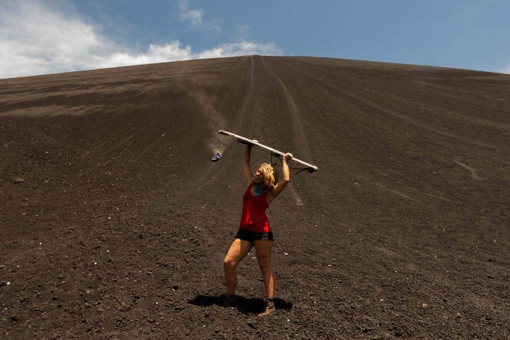 Annika met een board hoog in de lucht onderaan vulkaan Cerro Negro