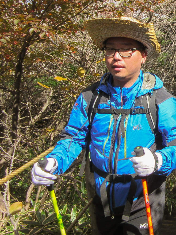 Korean hiker with walking sticks
