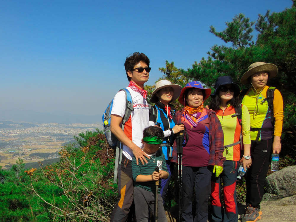 Korean family poses for a picture on top of a mountain