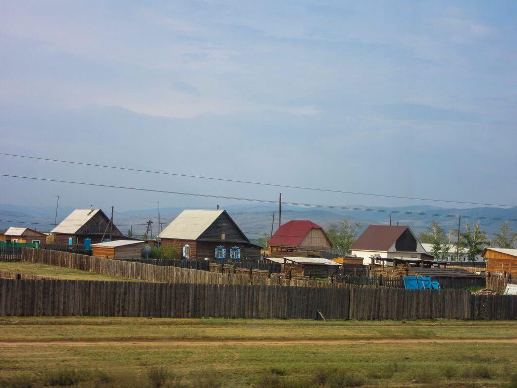 Huizen langs het spoor van de Transsiberië Express in Rusland