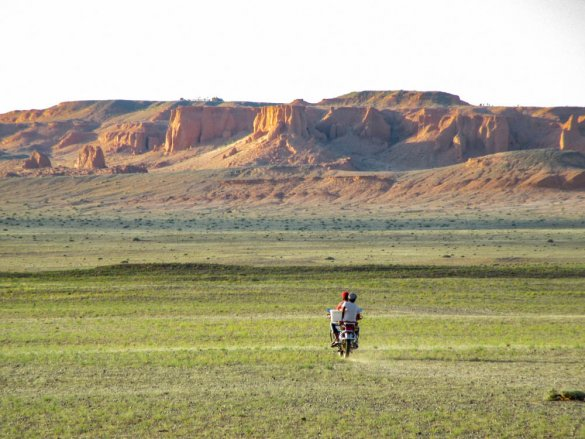 Mongolian youngs riding a motorbike in the Gobi desert near Bayanzag