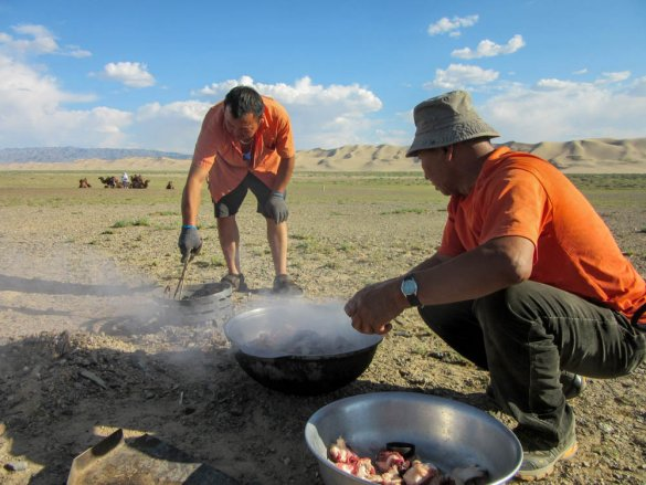 Mongolian tour guide preparing Mongolian barbecue underground near Khongoryn Els.