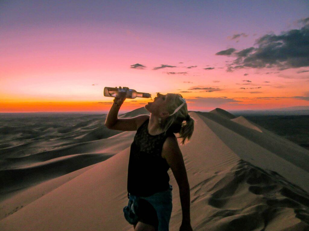 Annika drinking vodka on top of the sand dunes Khongoryn Els